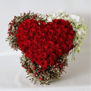 large red rose heart surrounded by hypericum, wax flower and orchids