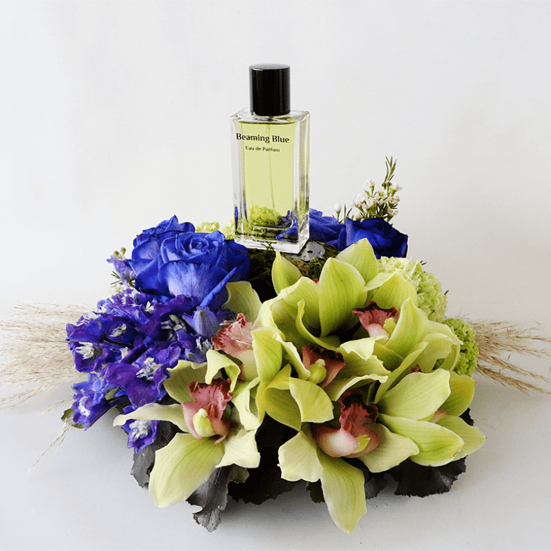 Cymbidium orchids with blue rose and delphinium in an arrangement with beaming blue perfume