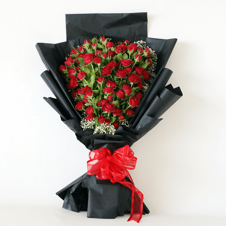 Red spray roses arranged in a heart shape with black paper