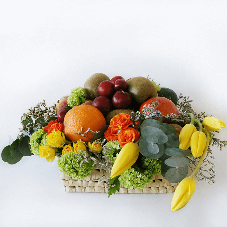 Fruit basket with oranges, tulips, plums, kiwi and flowers