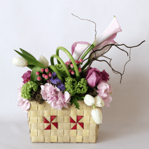 pink hydrangea, pink calla lily, white tulips, purple roses arranged in a basket
