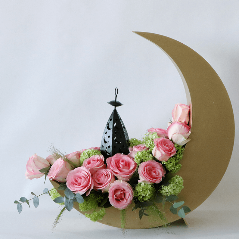 pink roses in a gold crescent moon with a lantern