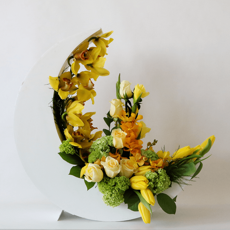 Yellow tulips, cymbidiums, orchids arranged in a white crescent moon