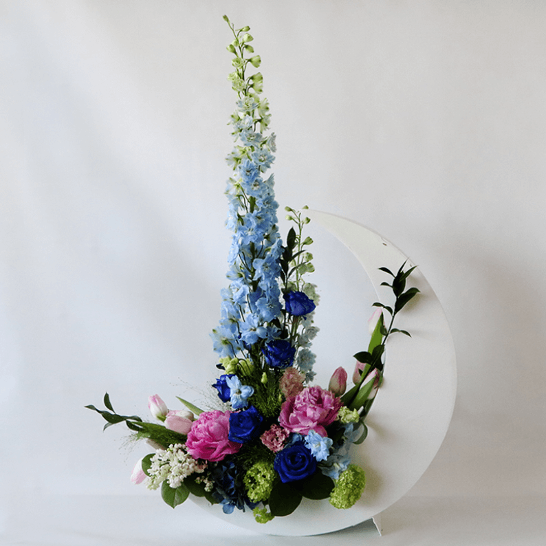 blue delphinium and pink peonies in a white crescent moon