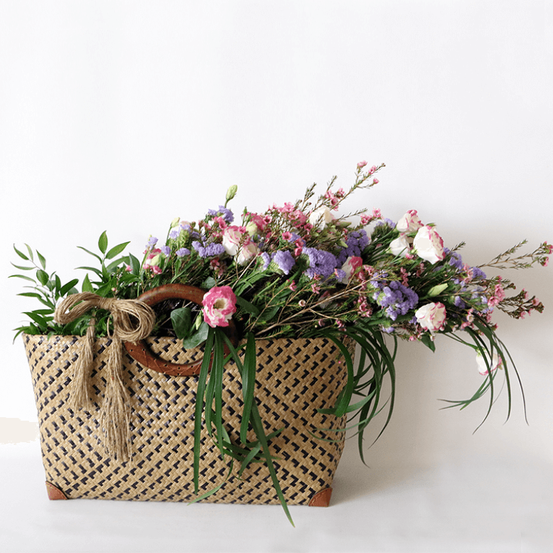 Natural looking flowers eustoma, wax flower, statice and greenery in a basket