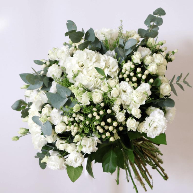 white hydrangea, white spray roses, white hypericum and eustoma in a bouquet