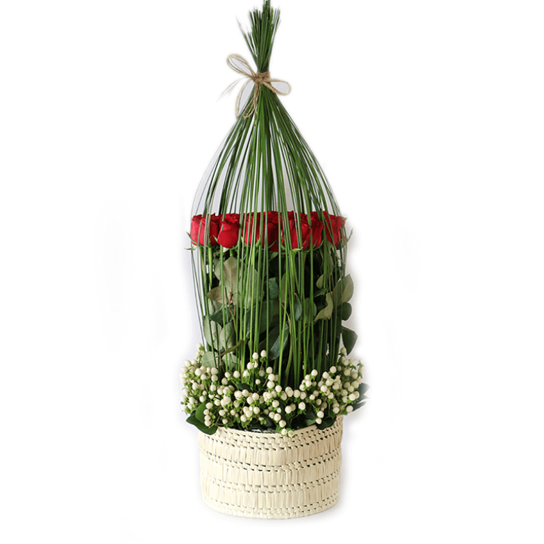 red roses surrounded by bear grass and hypericum arranged in a basket