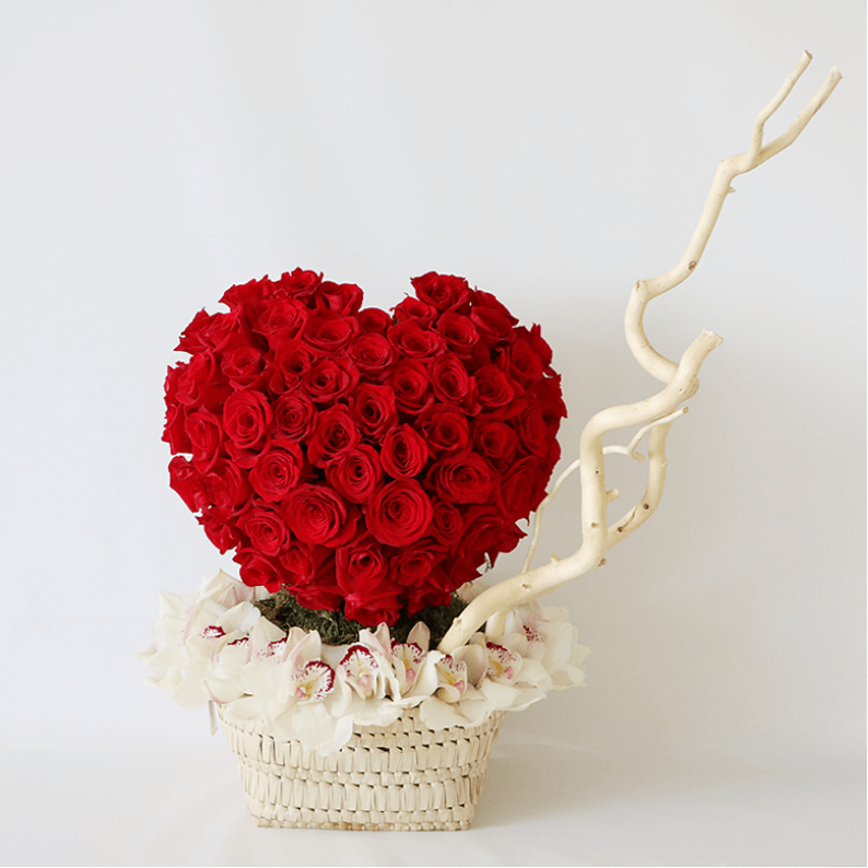 red rose heart surrounded by white cymbidium orchids and salex on a handmade basket