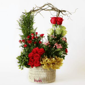 Red and green roses with spray roses, yellow cymbidium orchids in a basket