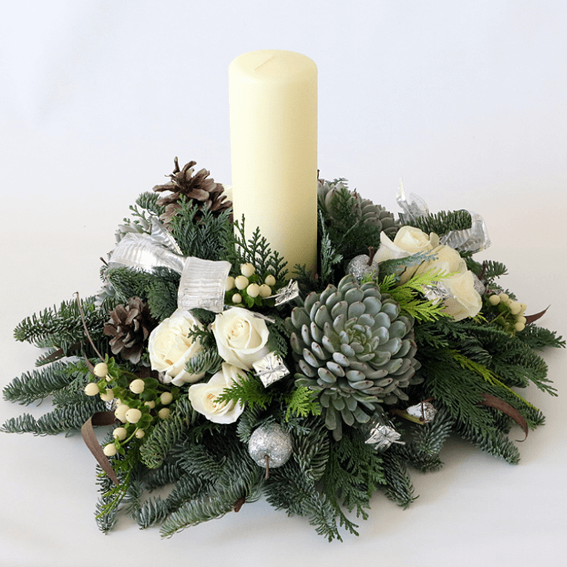 White candle and white roses with succulents and nordic spruce