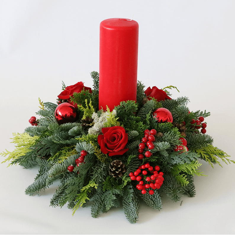 red candle and nordic spruce arrangement for christmas