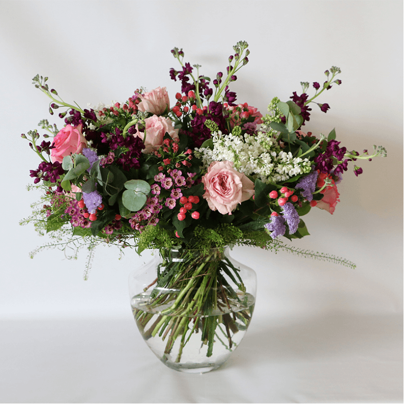 pink, purple white and green flowers arranged in a glass vase