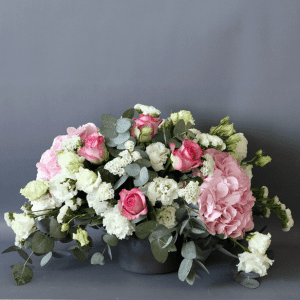 pink roses, pink hydrangea, white statice and eustoma arranged in a ceramic vase