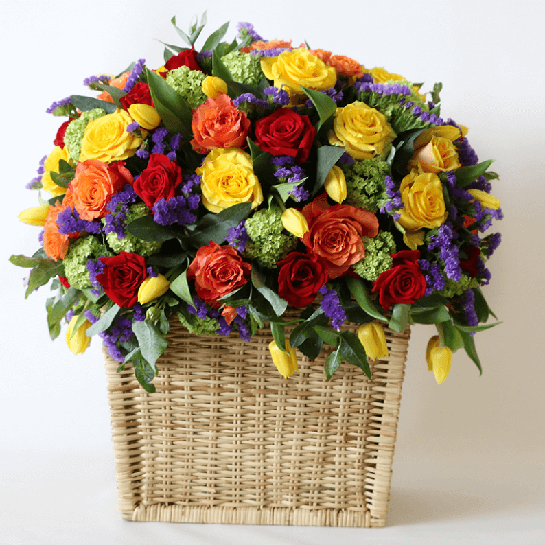 orange, yellow, red roses, with yellow tulips, purple statice in a basket