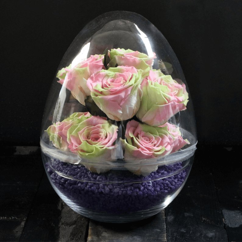 green and pink roses with purple stones in a dome