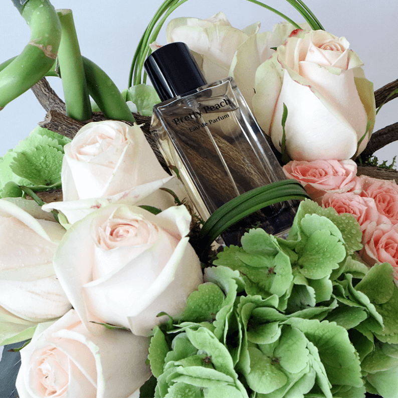 close up of pretty peach perfume with green hydrangea and peach roses