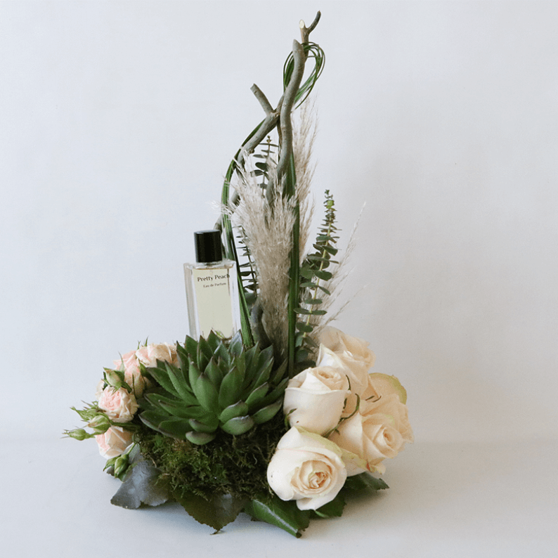 Pretty peach perfume with succulents and peach roses in an arrangement