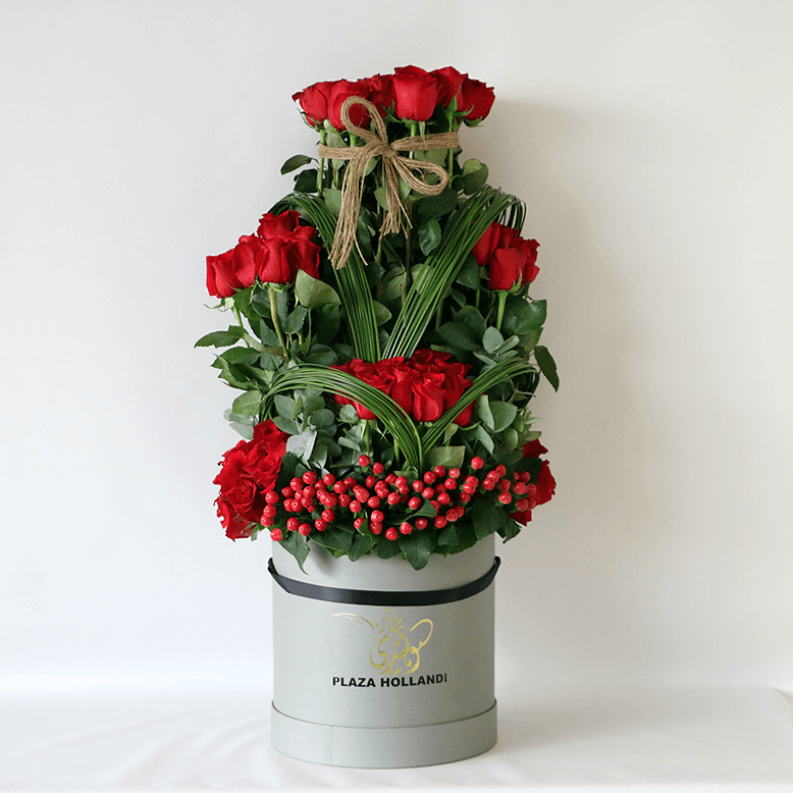 red roses, hypericum and greenery in a plaza hollandi hat box