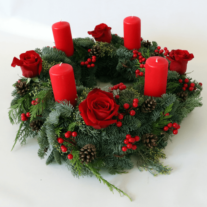 round wreath with four pillar candles and red roses