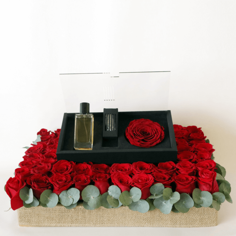 revealing red perfume arranged on filling with red roses and eucalyptus