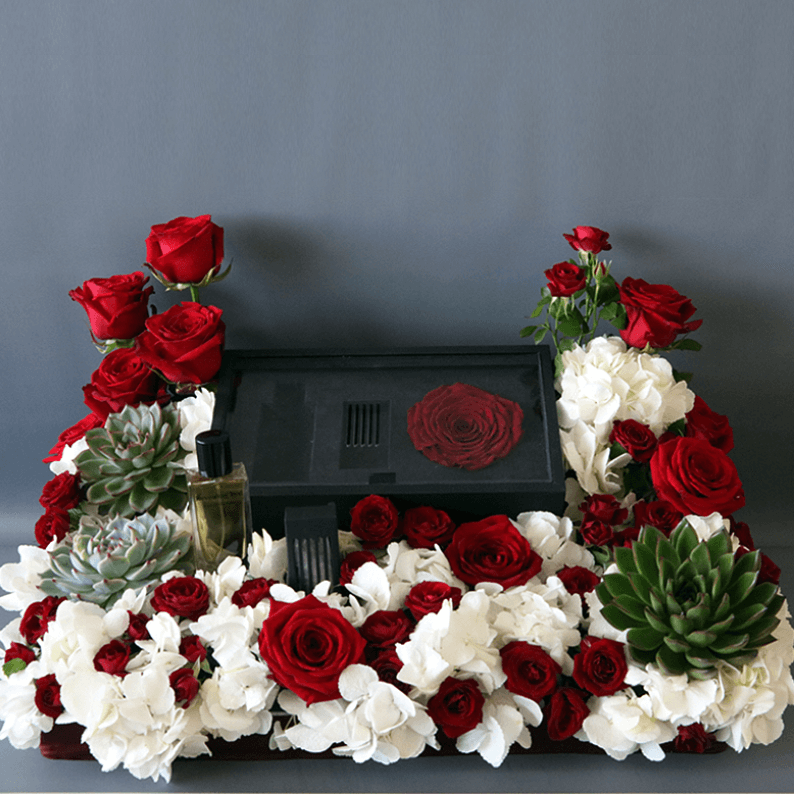 Box of revealing red perfume with oud and red roses and white hydrangea