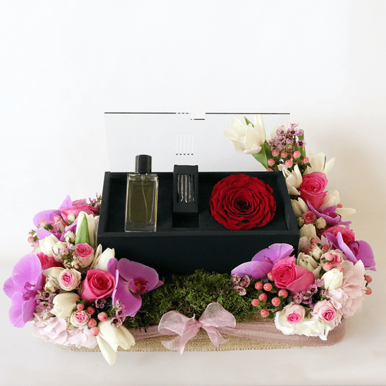orchids, roses and hydrangea surrounding a box of revealing red perfume with oud and rose amor rose