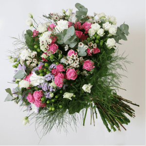 Pink spray rose, white spray rose, wax flower and hypericum in a bouquet