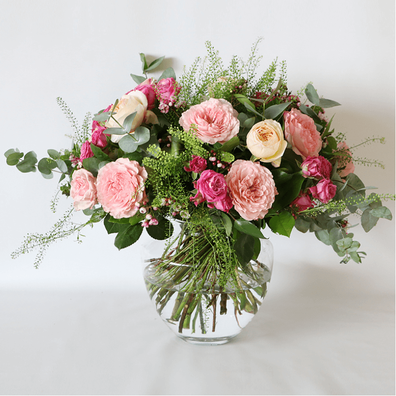 Pink garden roses, pink spray roses and greenery in a glass vase