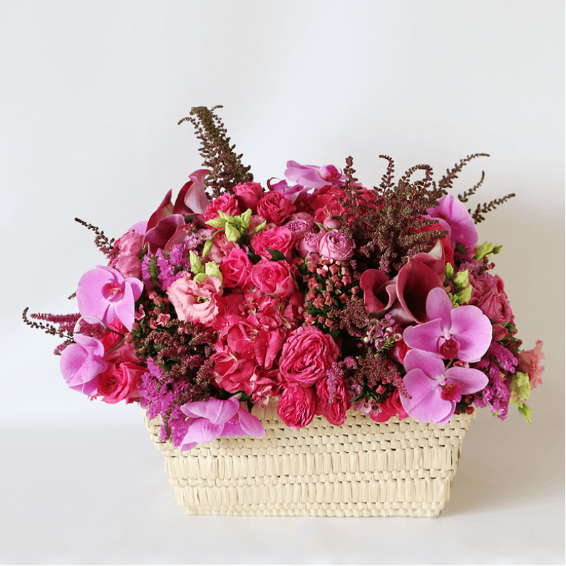 pink arrangement with phalaenopsis orchids, pink spray rose, pink astilbe, pink statice, pink calla lily, arranged in a basket
