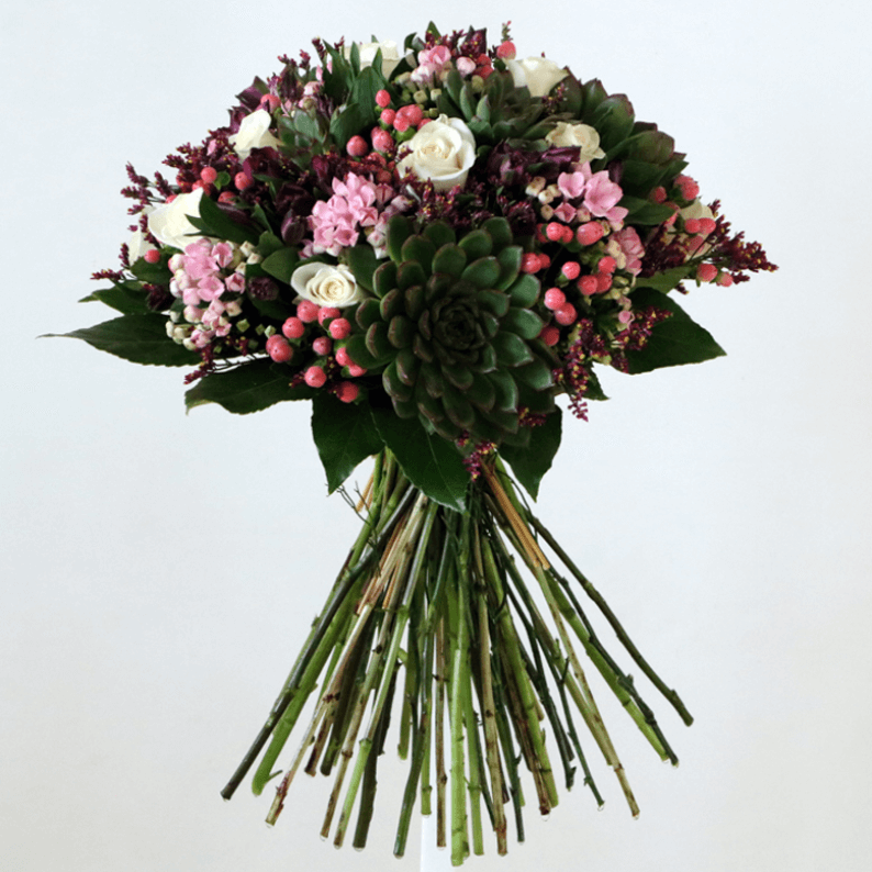 White roses, succulents, bouvadia, pink hypericum with leaves in a bouquet