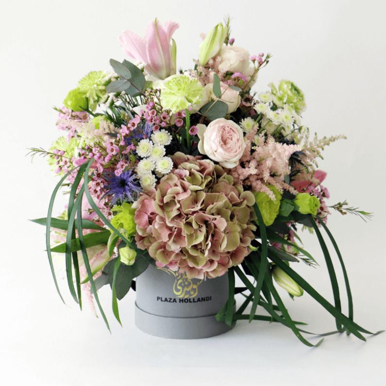 ranunculus, hydrangea, wax flower, eryngium, astilbe, lily arrangement in a Plaza Hollandi Hat Box