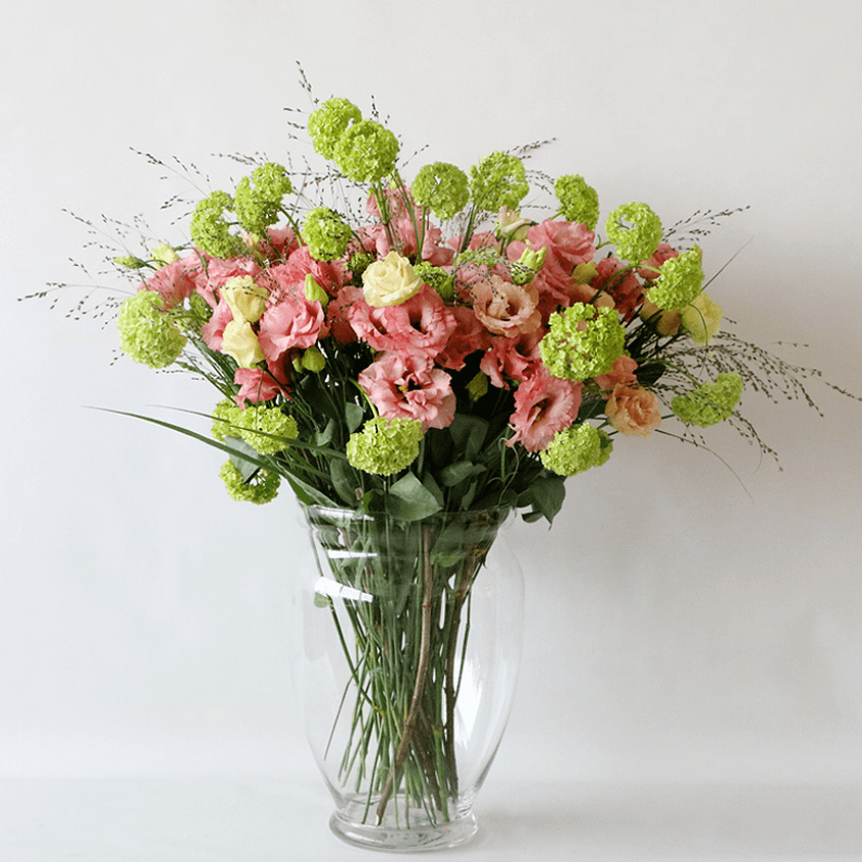 Pink eustoma in a glass vase with snowball and grass