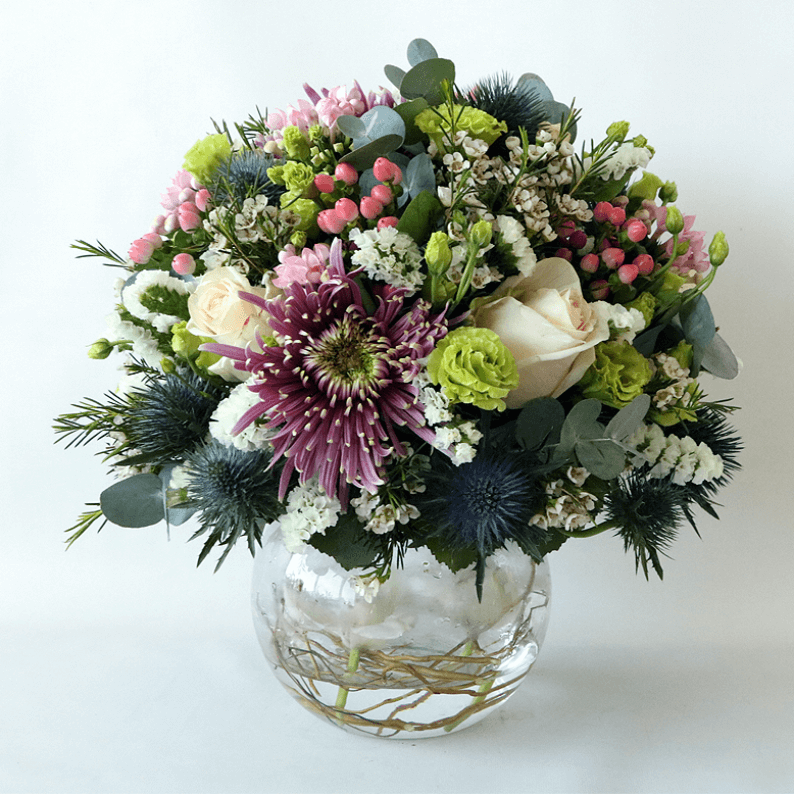 Round purple, green and white arrangement in a glass vase