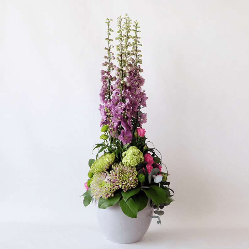 Tall delphinium arrangement with greenery in a grey pot