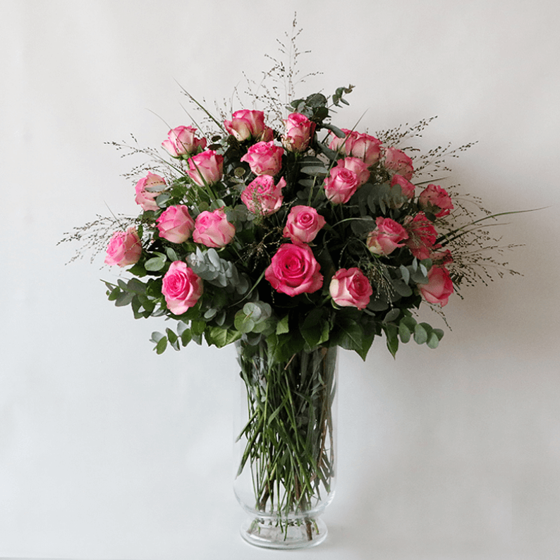 Pink roses in a glass vase with grass and eucalyptus
