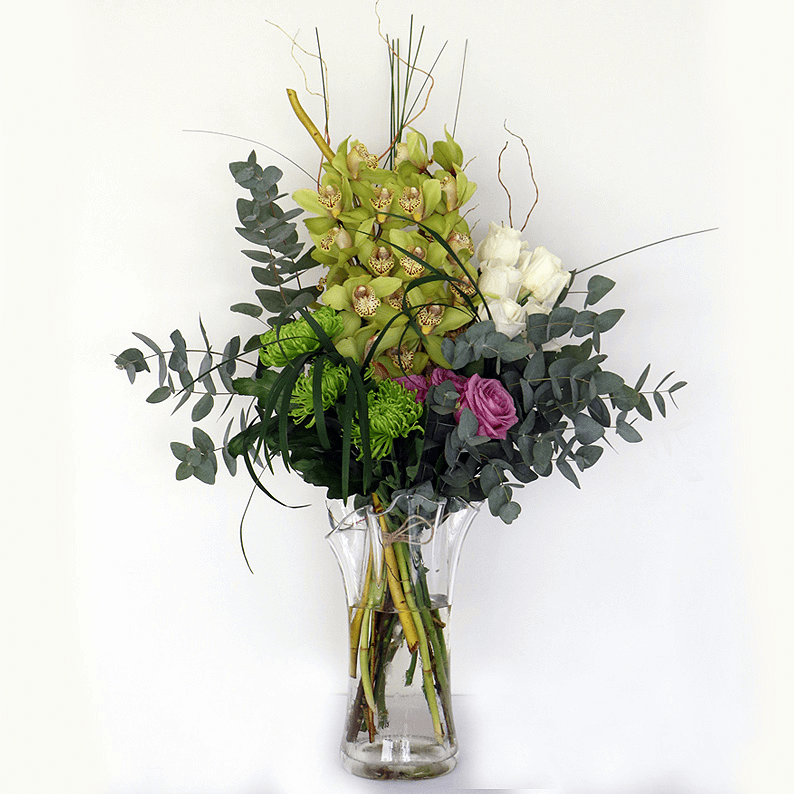 orchids, roses, eucalyptus and grass arranged in a glass vase