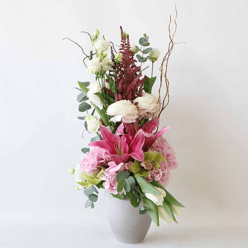 pink lilies, astilbe, hydrangea, tulips arranged in a grey pot