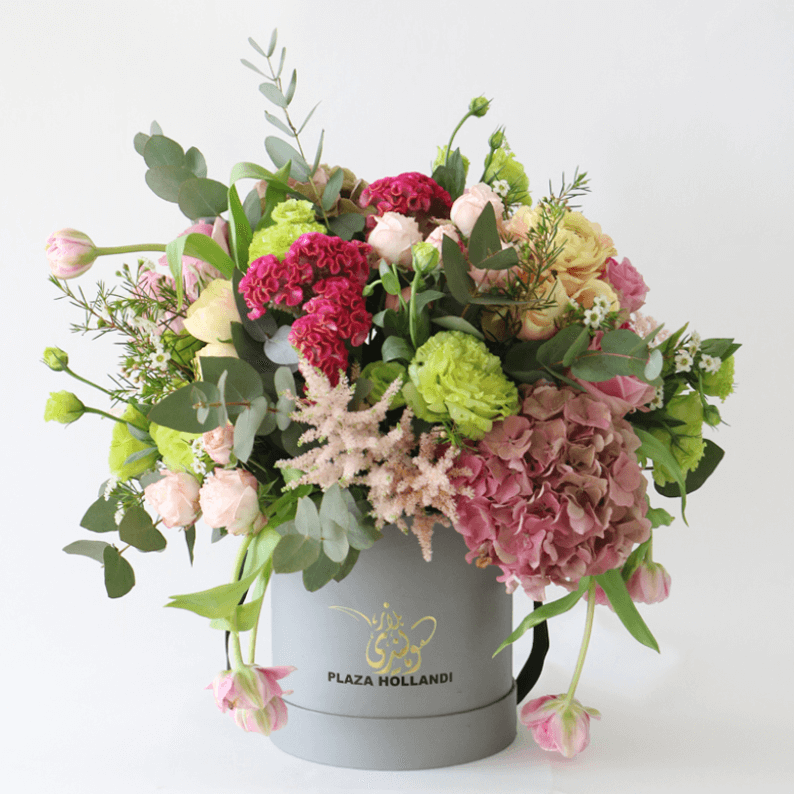 pink, green and peach flowers arranged in a hat box