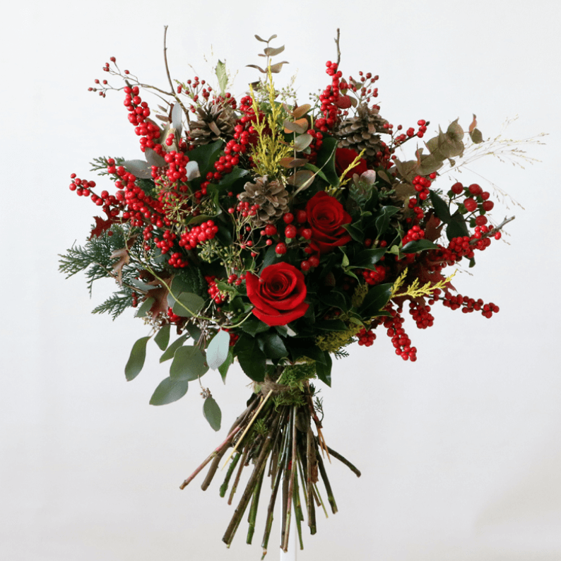 berries, red roses and leaves in a bouquet