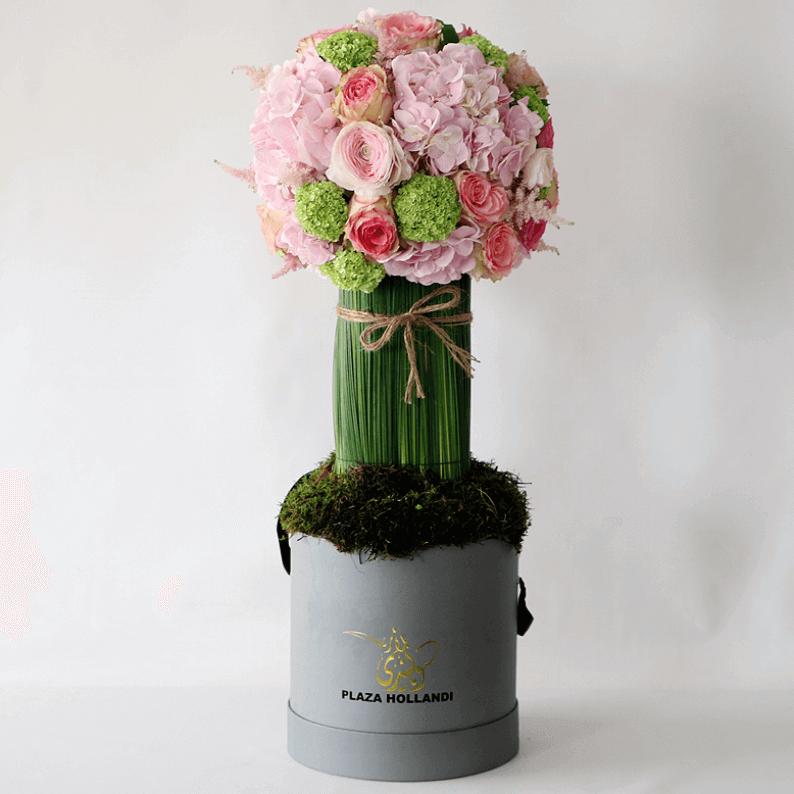 round pink flowers, hydrangea, ranunculus and steal grass on aa pillar in a plaza hollandi box