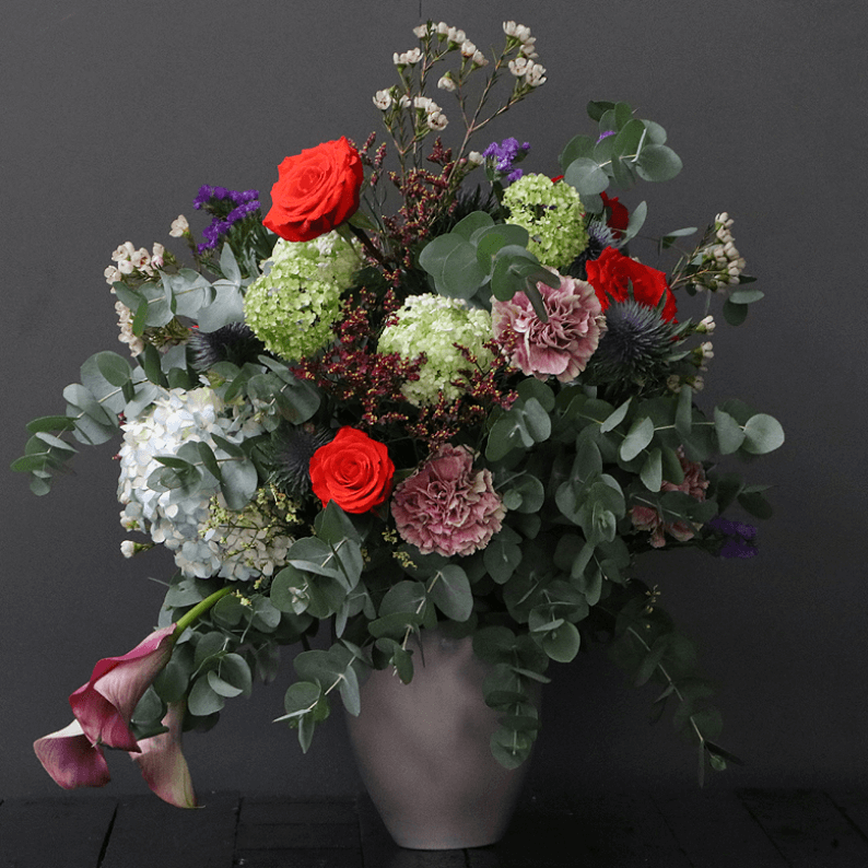 large natural floral design with red roses, carnations, snowball, wax flower and eucalyptus