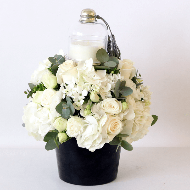 Scented candle with white and green flowers arranged including roses and hydrangea,