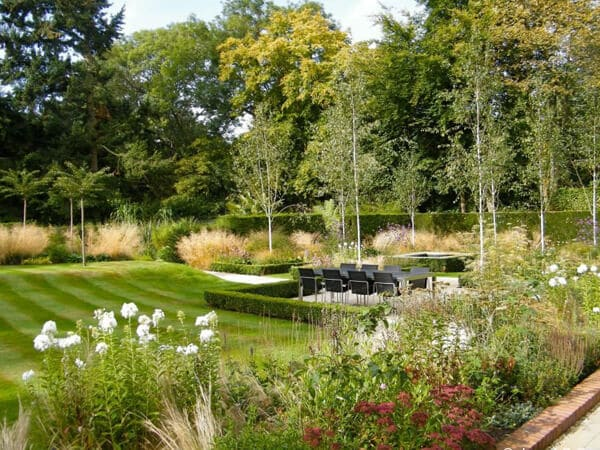Classic garden design with beach trees, grasses and dining area