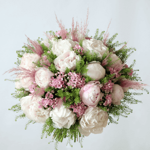 Pink and white peonies with bouvadia in a bouquet with pampas grass