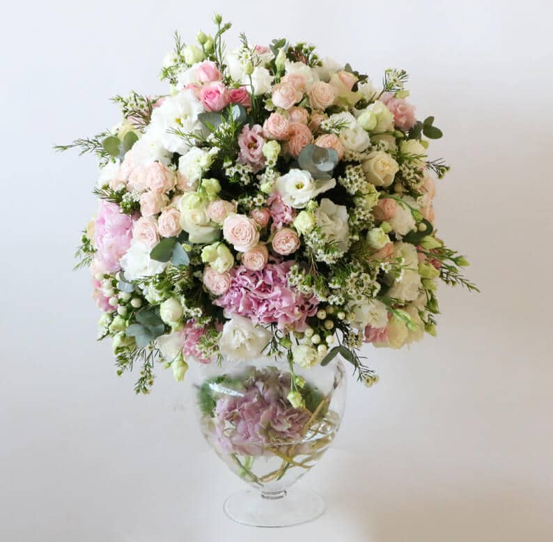 Pink, peach, white and green round flower arrangement on a glass vase