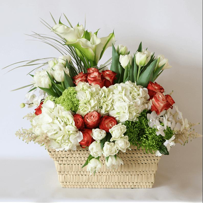 Large white hydrangea, white tulips, orange rose arrangement in a basket
