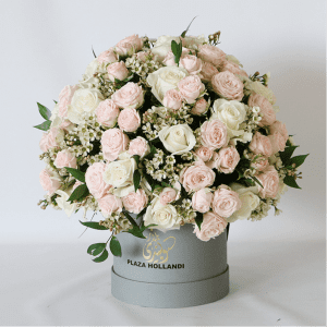 peach and pink spray roses in a round design in a hat box