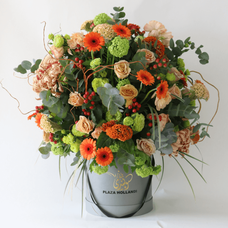 Orange germini, snowball, roses, hydrangea in a plaza hollandi box