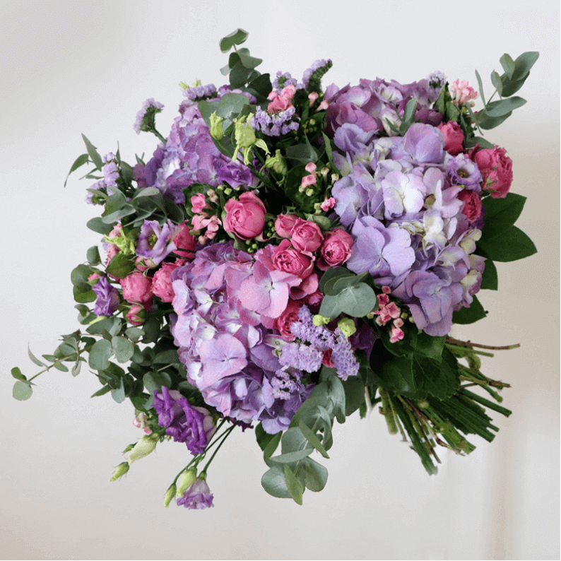 Purple hydrangea, pink spray rose and eustoma with greenery in a bouquet