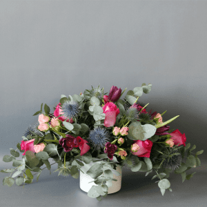 pink roses, purple tulips and eucalyptus in a white pot